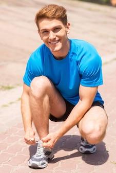 조깅을 준비합니다. 운동화에 신발끈을 묶고 야외에서 웃고 있는 잘생긴 남자