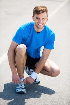 조깅을 준비합니다. 운동화에 신발끈을 묶고 야외에 서 있는 동안 웃는 남자의 상위 뷰