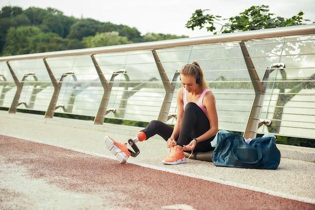 Готовится к запуску молодая женщина в спортивной одежде и наушниках с перевязкой протеза ноги