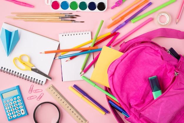 Готовимся к концепции школы. фото розового рюкзака и красочных канцелярских принадлежностей, изолированных на пастельно-розовом фоне, сверху сверху.