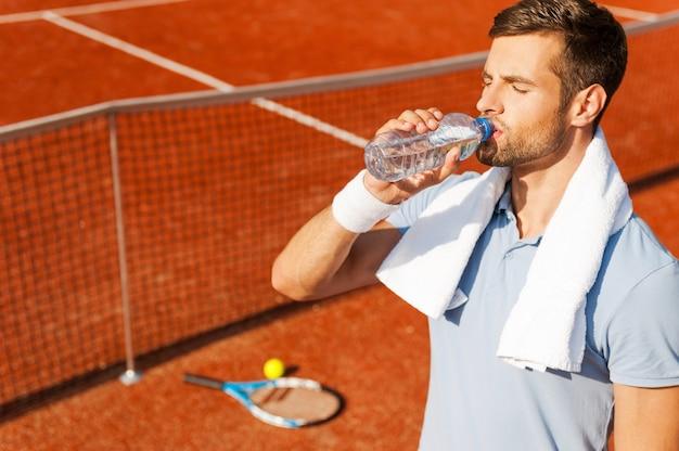 ゲーム後にリフレッシュする。テニスコートに立っている間水を飲むポロシャツとタオルの喉が渇いた若い男