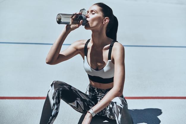 Обновляюсь. вид сверху молодой женщины в спортивной одежде с питьевой водой