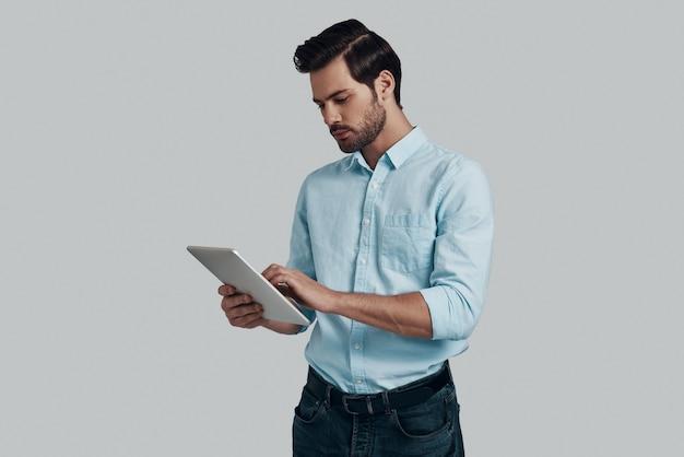 物事を成し遂げる。灰色の背景に立ってデジタルタブレットを使用して作業する集中した若い男