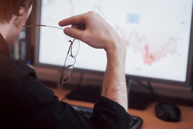 Анализ данных. закройте молодого бизнесмена, который держит очки и смотрит на gff, работая в творческом офисе