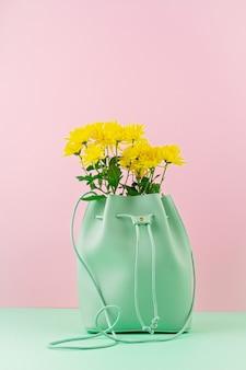 花を持つ美しい女の子バッグ。女性の都会的なファッション、ショッピング、gfitのアイデア、春と夏のスタイル