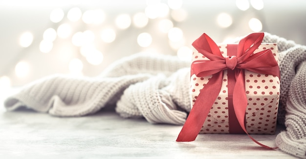 Подарок в красивой коробке с красным бантом и серым пледом