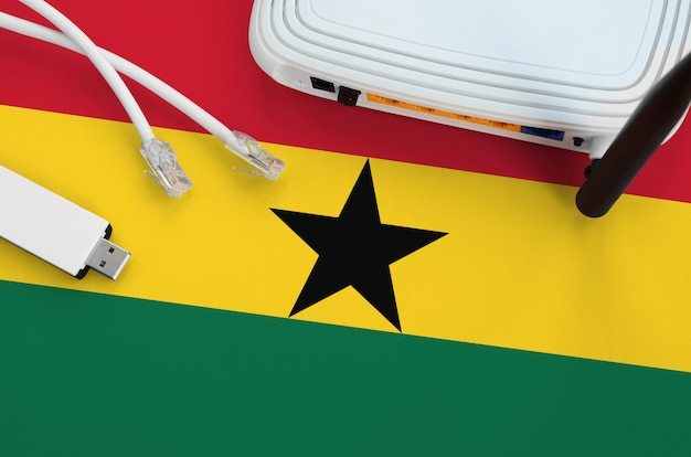 Ghana flag depicted on table with internet  cable, wireless usb wifi adapter and router. internet connection concept