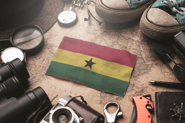 Ghana flag between traveler's accessories on old vintage map. tourist destination concept.