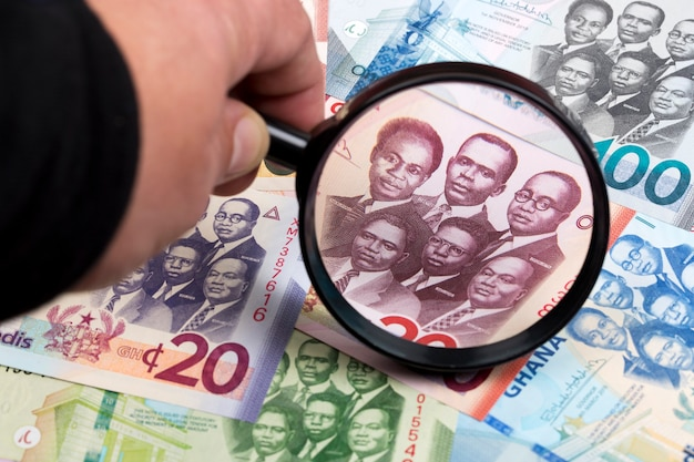 Ghanaian cedi in a magnifying glass