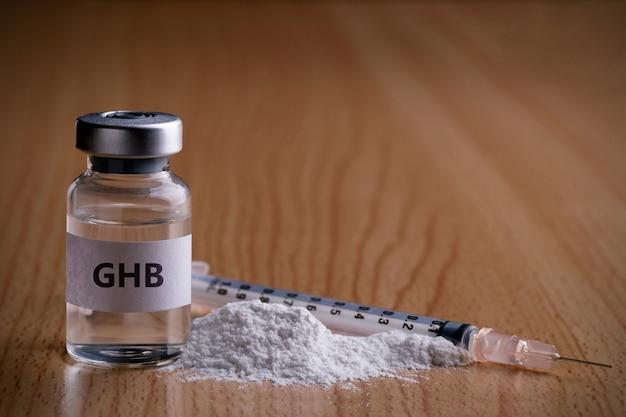Бутылка ghb с лекарственным порошком и инъекционной иглой на деревянной поверхности ghb