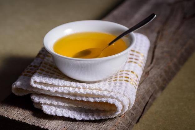 Масло топленое из индии в белом контейнере посуды на деревянном столе.