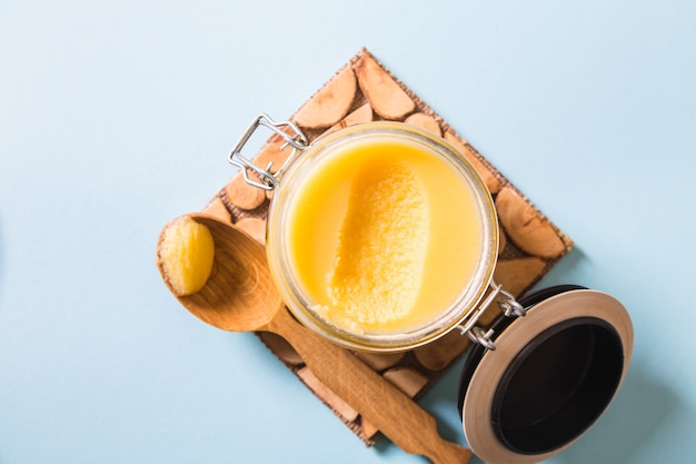 Ghee or clarified butter in jar and wooden spoon on blue background. top view. copyspace. ghee butter have healthy fat and is a common cooking ingredient in many of the indian food Premium Photo