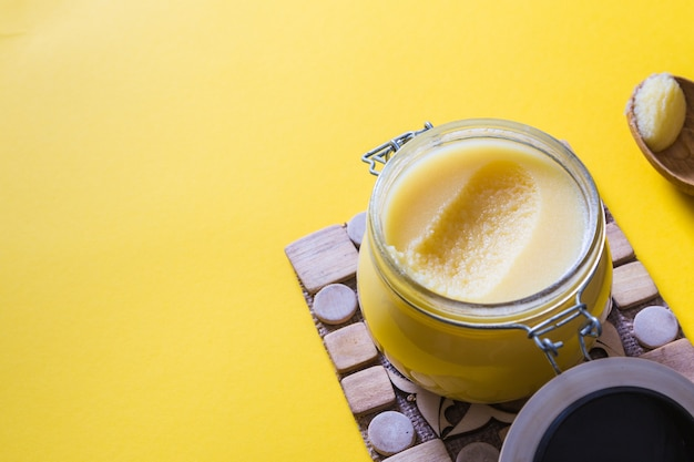 Ghee or clarified butter in jar and wooden spoon on yellow background. top view. copyspace. ghee butter have healthy fat and is a common cooking ingredient in many of the indian food