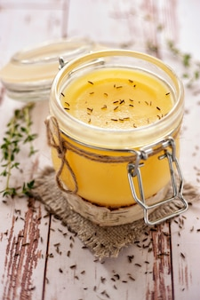 Ghee oil according to the traditional indian recipe. cooked with cumin and fresh herbs. stored in a glass jar. close up and vertical view.