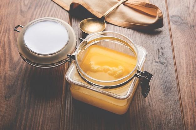 Топленое масло или топленое масло крупным планом в деревянной миске и серебряной ложке, выборочный фокус