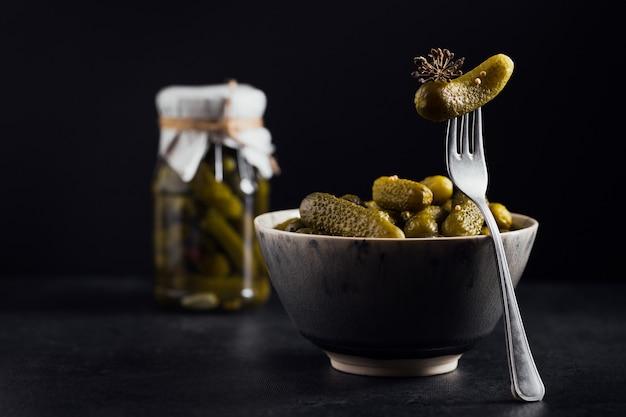 Корнишоны, маринованный огурец на вилке, миска маринованных овощей на черном