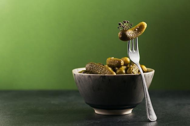 Корнишоны, маринованный огурец на вилке, миска маринованных овощей на зелени.