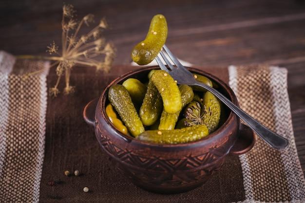 Корнишоны, маринованный огурец на вилке, миска с маринованными овощами на деревенском деревянном фоне. чистое питание, концепция вегетарианской пищи