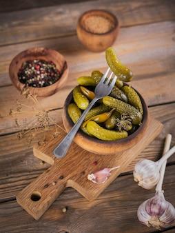 ガーキンス、フォークにきゅうりのピクルス、素朴な木製の背景にマリネした野菜のボウル。きれいな食事、ベジタリアン料理のコンセプト