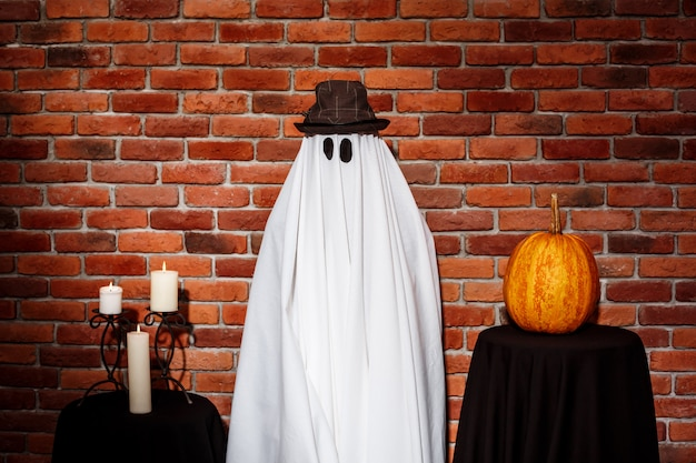 Ghost in hat posing over brick wall. halloween party.