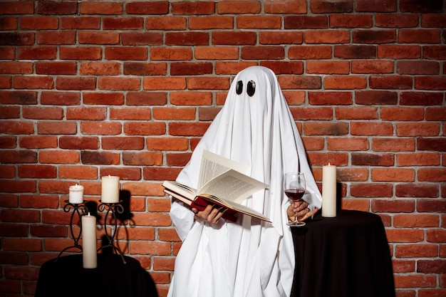 벽돌 벽을 통해 책과 와인을 들고 유령입니다. 할로윈 파티.