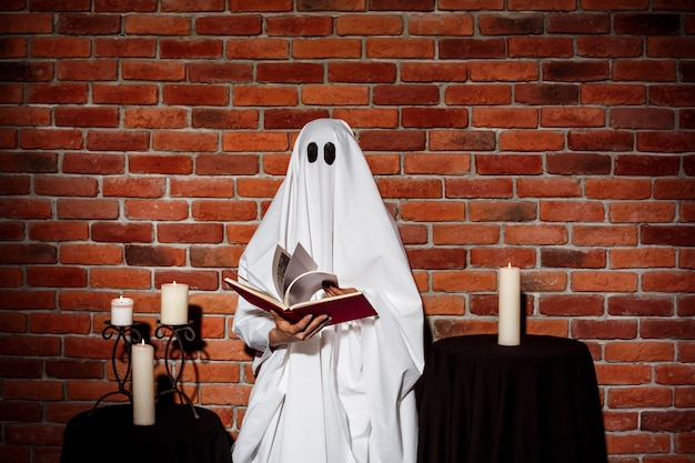 Ghost holding book over brick wall. halloween party.