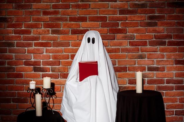 Призрак держит книгу над кирпичной стеной. halloween party.