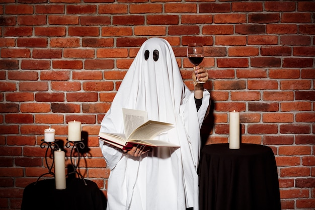 Ghost holding book and wine over brick wall. halloween party.