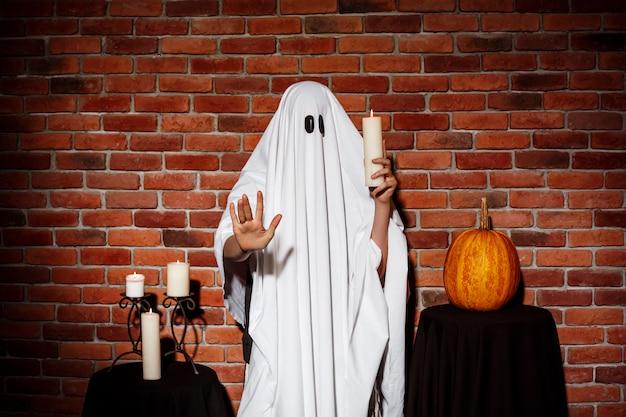 Fantasma che tiene la candela alla festa di halloween