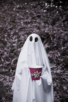 Ghost holding popcorn box with popcorn in air