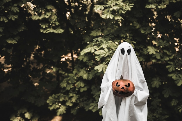 Ghost holding pumpkin and standing in forest