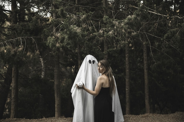 Ghost and lady holding hands in park