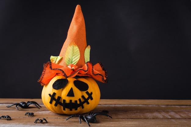 ゴーストカボチャヘッドジャックランタン怖い笑顔は木製のテーブルに帽子とクモを着用