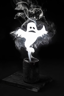 Ghost in smoke from candle on black background, frightening restless spirit, halloween concept.