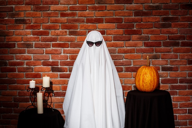Ghost in sunglasses posing over brick wall. halloween party.