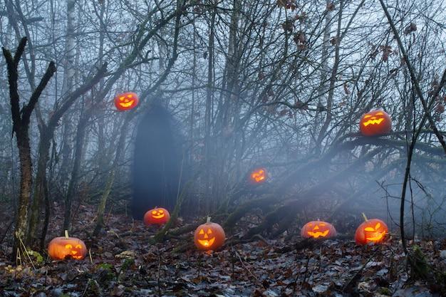 Призрак с тыквами на хэллоуин в ночном лесу