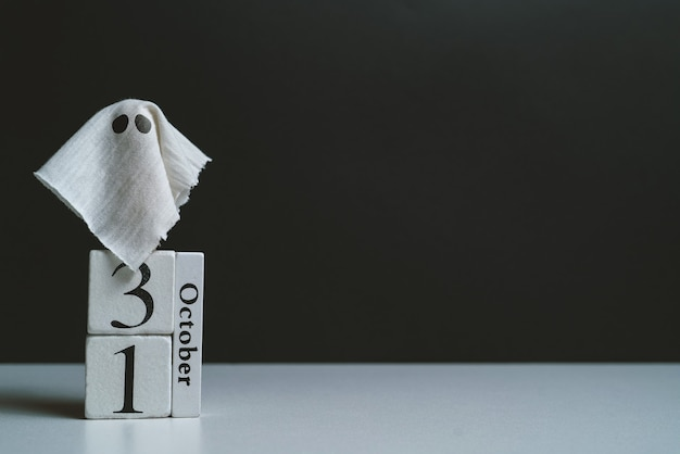 The ghost with the october calendar and bats with copy space halloween holiday
