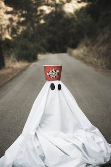 Ghost with popcorn box on head sitting on countryside road