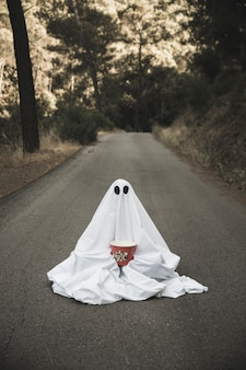Ghost with popcorn box sitting on countryside road