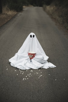 Ghost with popcorn box sitting on road with spreading grains
