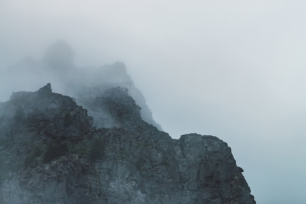 Ghostly atmospheric view to big cliff in cloudy sky.
