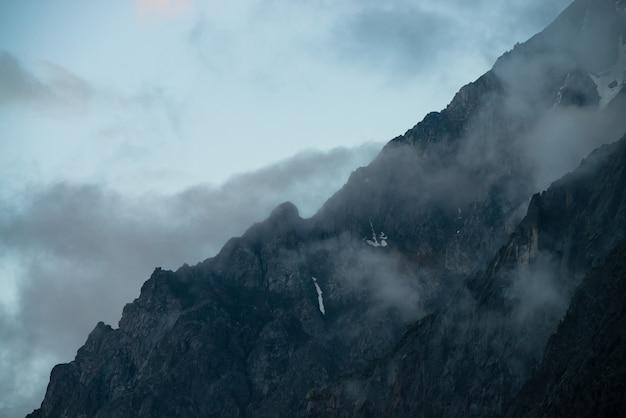 濃い霧の中の木がある幽霊のような巨大な岩。雪に覆われた神秘的な巨大な山。山の早朝。突き通せない霧。暗い大気の不気味な風景。静かな神秘的な雰囲気。