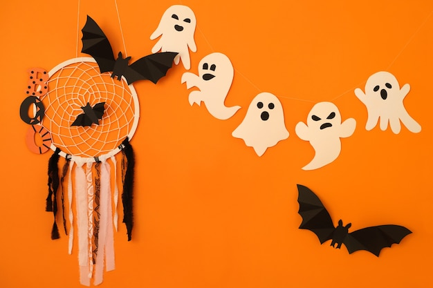 オレンジ色の背景に蜘蛛の巣を持つ幽霊コウモリとドリームキャッチャーはハロウィーンのコンセプトです