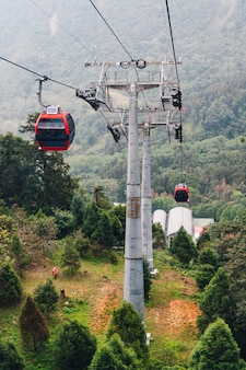 Giant cable posts of gondola lifts place amid green trees in the area of sun moon lake ropeway.