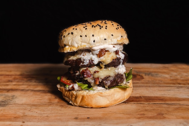 Giant double hamburger on top of a wooden table with black background.