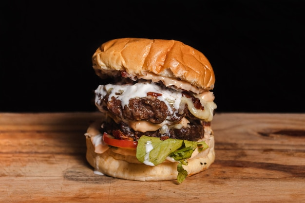 Giant double hamburger with condiments on top of a wooden table with black background.