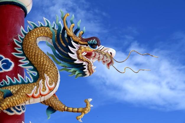 Гигантская золотая статуя китайского дракона на фоне неба
