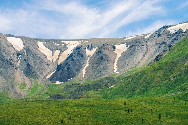 青空の下で晴れた日に針葉樹と緑の谷の上に汚れた雪と巨大な灰色の岩の山腹。雄大な自然の素晴らしい高原の風景。