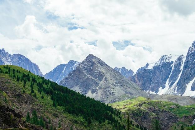 Гигантская гора формы пирамиды около снежных гор.
