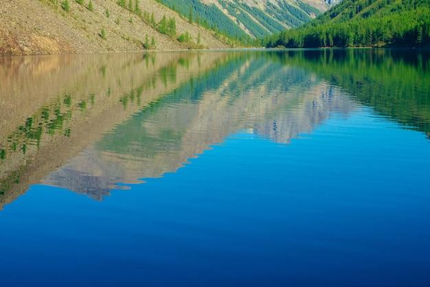 巨大な山々が日光の下で山の湖のきれいな水に反射しました。